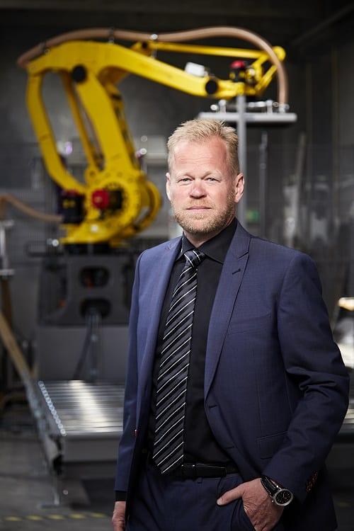 Henrik Anker foran en robot